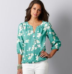 A gorgeous floral blouse finished with slightly puffed shoulders is the essence of relaxed femininity. Split neck. 3/4 sleeves. Banded trim and gathered details at neckline. Pearlized buttons. Gathered elasticized cuffs and hem.