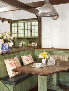 Dining Nook    A built-in banquette offers dining space in the kitchen, where lights salvaged from a warehouse add a touch of industrial appeal.