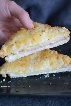 A hand lifting a half slice of a Croque Monsieur.