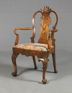 A George II walnut and marquetry shepherd's crook armchair circa 1735 the back centered by a stylized shell carved with scales over a solid shaped splat inlaid with a flower-filled vase and foliate scrolls flanked by scrolled stiles over an incurving padded drop-in seat covered in associated floral needlework over a serpentine seatrail centred by a scale-carved shell on stylised anthemia-headed cabriole legs carved with acanthus, with scrolled brackets and foliate-carved scrolled feet