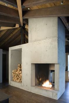 love this concrete fireplace with built in storage