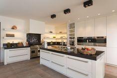 Ruime Tieleman-keuken met werk- en spoeleiland. Het dikke granieten aanrechtblad, het fornuis en de robuuste keukengrepen geven een rijke uitstraling. Geplaatst door eigen vakmensen in Brasschaat (België).