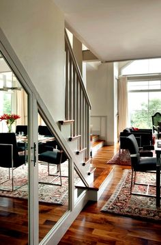 Disguising under stair storage with mirrored paneled doors.