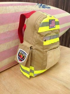 Ain't she purty.? Two pockets are on the front. The white part was an elbow pad. The pocket behind that is the cuff. A radio pocket on the side,this back pack is a campers, runners,bikers dream. Let the rain come down because all your gear will stay dry. Backpack bag made by hand with recycled firefighter bunker gear!