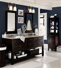 small bath: balance dark sea blue walls with white. Dark: walls,  wood vanity, baskets, shelf unit with glass doors;  Light: white fixtures, floor, ceiling, trim, rug, art,windoww shade (navy trim) towels, plus natural light to balannc