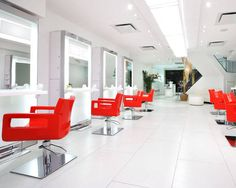 In this midtown Manhattan salon, red vinyl styling chairs add a striking pop of color to the gleaming-white minimalist interior.
