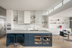 sliding cabinet doors over open shelving with continuous marble-style backdrop from backsplash