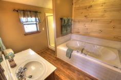 Sasquatch Ridge Pigeon Forge vacation rental cabin rustic bathroom with whirlpool bath. This bathroom is on the upper level and accessible through the hall or master bedroom.