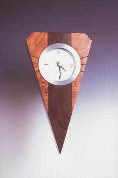 Howard Griffiths - Maple Burl & Walnut Wall Clock This striking wall clock contains Maple Burl on the outer edges with a strip of Walnut down the center and measures 10x5.5x2. No two pieces that Howar