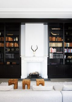a white fireplace juxtaposed with black bookshelves - balance.