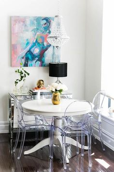 A clear beaded chandelier by Overstock illuminates a white Ikea Ingatorp Dining Table lined with Ghost Chairs.
