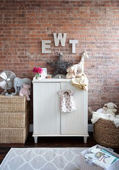 exposed brick wall, white small changing table, gray moorish tiles rug, stacked storage baskets and wood letters.