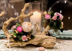 using the driftwood adding your floral with burst of color and of course candles (yes of course) then adding just a few starfish for the beach decor