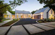 Modern Farm House in Dallas, Texas with a large driveway and a two car garage. This exterior features a board and batten siding in Sherwin Williams color Agreeable Gray, and basic steel garage doors.