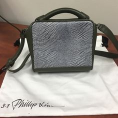 3.1 Phillip Lim Ryder - Lizard Embossed Like new! Tags, dust bag, and authenticity card included. Slight creasing near handle bars and sides of bag. Small scuff on bottom of bag. Please look at pictures. Otherwise in great condition.   Olive green, white embossed lizard leather panel at front, single top-handle, gunmetal-tone hardware on top, top zip closure, interior zip pocket, shoulder strap, fully lined. Cowhide leather.  Product measures: Length 17cm / Width 9cm / Height 17cm / Handle…