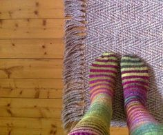 Rainbow striped socks (I'm guessing these were knit with Noro yarn). Love the rug, too!