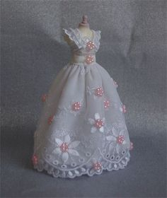 Daisy Daisy. Beautiful pure white Wedding gown on 5 inch top quality mannequin. Dupion silk underskirt overlaid with lace and adorned with pastel pink pearl rings. Very pretty gown.