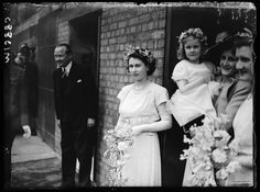 Wearing a simple ankle-length dress and garland of flowers in her hair, Princess Elizabeth serves as bridesmaid to friends at the Savoy Hotel in London in May 1946.