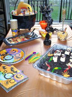 Kids Halloween party table with graveyard pudding cake.