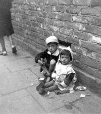 Niños hambrientos sobre la acera en el gueto de Varsovia