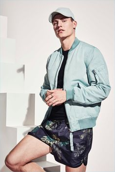Model Mikkel Jensen sports a teal bomber jacket and swim shorts from River Island's high summer 2017 collection.