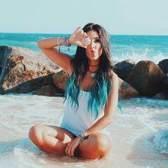 Chica sentada en la playa con una concha en la mano