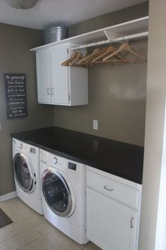 Contemporary Laundry Room with Built-in bookshelf, limestone tile floors, flush light