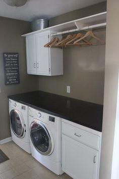 Contemporary Laundry Room with Built-in bookshelf, limestone tile floors, flush light