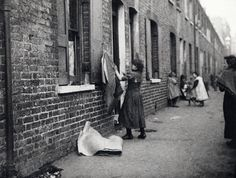 Child sack-making in an East End court , London, 1900
