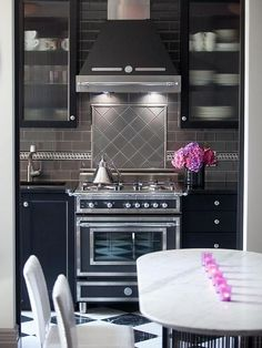 Again with the incredible gray subway tile  Art Deco Kitchen Design with Dark Furniture - Courtesy of HGTV - Deco Range & Hood