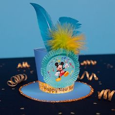 Mickey's New Year Celebration Hat. Nodig: Bijlage, Elastieken koord, veren, Cupcake vormpjes, Dubbelzijdig tape. Werkwijze:Zie beschrijving in bijlage. http://static.spoonful.com/sites/default/files/new-year-mickey-top-hat-printable-1212.pdf