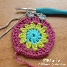 Doing dc stitches in gray yarn around a crocheted circle