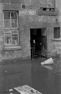 Boy negotiating flooded entry in tenement block Maryhill 1971