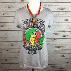 """[Boho Luxe] Grateful Dead Graphic Tee Jamaica Cool Super soft band graphic tee. Awesome Grateful Dead Jamaica 1982 colorful design. Cap sleeves. Pairs perfect with cutoffs for summer and festivals! Marked kids XXL. I think fits like a women's small or fitted medium. Check measurements   Fabric: 60% Cotton 40% Polyester  Bust: 18"""" Length: 25"""" Condition: EUC. No flaws.  No Trades! Grateful Dead Mercantile Tops Tees - Short Sleeve"""
