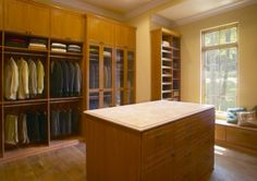 #closet A beautiful custom closet with island and glass door upgrades.  A high ceiling allows for additional storage above the hanging sections.