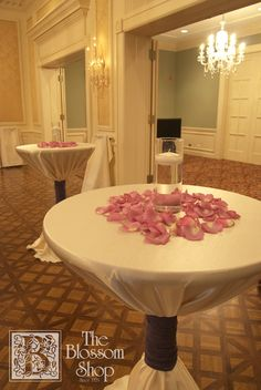 Bistro Tables With Lavender Rose Petals And A Tall Cylinder Vase Floating Candle