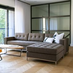 Incredible Living Room Design Idea with Wooden Flooring and L Shaped Brown Fabric Tufted Sofa Design feat White Black Pillows and Wooden Coffee Table using Black Iron Handle also Curtains