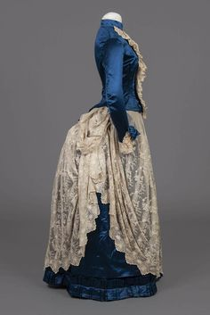 1886 Bustle Dress Side View. Blue Satin and Lace with separate lace Jabot.