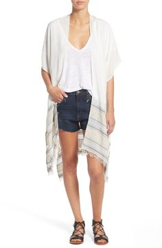 Woven patterned stripes define this super cute lightweight poncho that effortlessly doubles as a scarf.