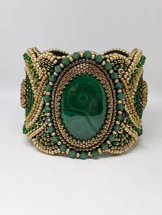 This is a beautiful Bead Embroidered Cuff bracelet with a 75ct Malachite center stone . Hand made with Swarovski crystals and seedbead. It measures 7.5 inches long. Hook and eye clasp for seemless finish and covered with ultra Suede for comfort.