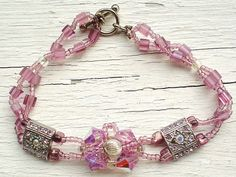 """Mauve and Silver Flower bracelet features Swarovsky crystals and components, Sterling Silver bead, glass cubes and seed beads. 7.5"""""""