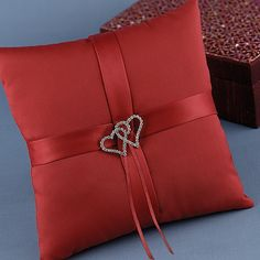 This Claret satin ring pillow with satin ribbon accents and silver-plated, rhinestone heart adornments speaks the language of love, Red with hearts. Having a red, black, and white theme wedding, this works great.