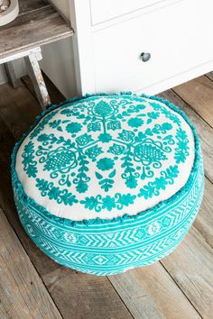 The Turquoise Embroidered Floor Pouf is a beautiful textile that features intricate embroidery, 100 cotton fabric, and bright turquoise color.