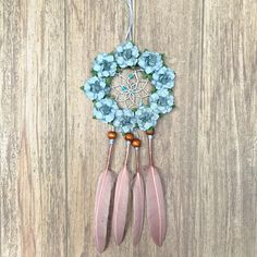 Handmade small dream catcher featuring dusty blue paper roses. The diameter of the hoop measures 3 inches and is covered in tan genuine suede lace. The interior is weaved with blue-gray thread and decorated with blue beads. Wooden beads hold the mauve feathers in place.  Item is made and