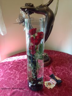 Art deco lady bronze statue with glass cylinder  vase flower arrangement for Red, Black and White Gangster theme Murder Mystery party, add cards and bow tie to props for table. Fully submerge the roses for more drama, they'll last well for the party.