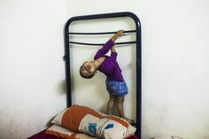 Fabha, 2 years-old, and Oliur Rahman's daughter, plays holding herself from a disassembled bed as she waits to get evicted in Madrid, Spain, Friday, Sept. 12, 2014. The landlord's loss of the apartment to a bank is causing Rahman family's eviction. Oliur Rahman and his wife Hamida and their two children of 2 and 6 years old moved into the foreclosed apartment paying a rent of 300 euros ($388) a month. With a monthly pay-check of only euros 700 a month ($ 907) this was his only option.