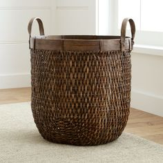 Shop Halton Large Basket.  Woven of rattan, this handy basket is shaped tall for lots of storage.   Solid rattan contrasts with the textural body, shaping a decorative rim and handles.