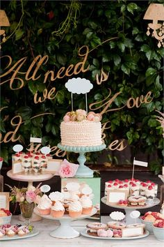 """I LOVE this dessert table! I love how the different sweets are displayed and also the """"All we need is love"""" in the background."""