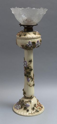 "ZSOLNAY BANQUET LAMP Pecs, Hungary, Late 19th/Early 20th Century Decorated in high relief with polychrome flowering vines on a cream-colored ground. Includes associated molded and frosted clear glass shade. Impressed factory mark and numbered 3988. Height to top of base 23.5"". 16/531U"