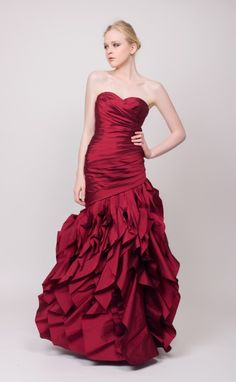 A wine red evening gown perfect for a silky seductress. Sweetheart neckline and detail along the bodice leading to a ruffled cascading skirt.